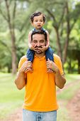 cheerful indian father carrying son on his shoulders in the park