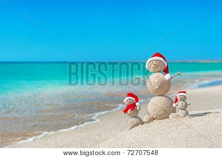 Snowmans Family At Sea Beach In Santa Hat. New Years And Christm