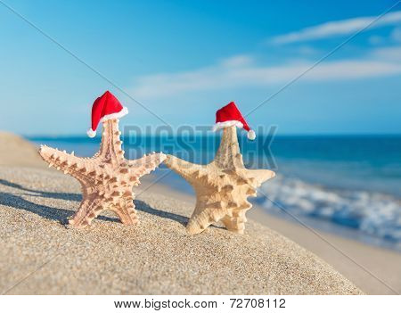 Sea-stars Couple In Santa Hats Walking At Beach. Holiday Concept