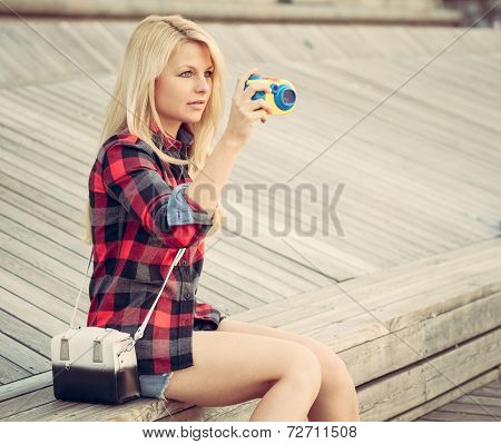 Attractive Blond Woman Sitting On The Wooden Floor And Photographed With A Toy Camera