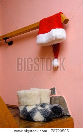 red santa hat and warm woolen boots at home interior - christmas or new year's concept for postcard