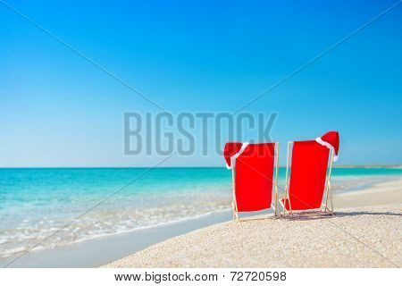 Santa Hat On Chaise Longues At White Sand Beach Against The Sea