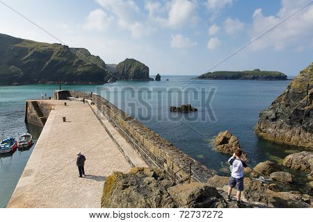 Tourists and visitors Mullion harbour near St Austell Cornwall England UK in late summer with blue s