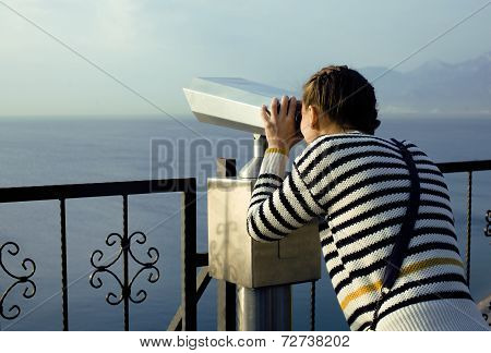 young woman looking through telescope at sea viewpoint in Ataturk park
