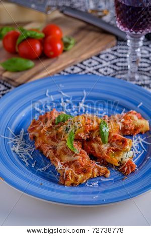 Cannelloni Pasta Dish With Tomatoe Sauce On A Blue Plate With Tomatoes In The Background And Wine