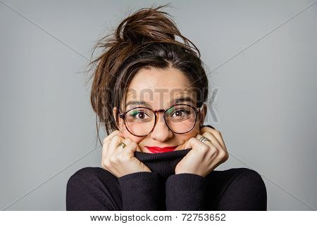 Real girl with glasses and red lips taking her neck sweater