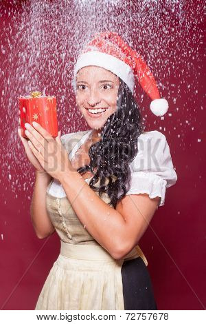 Christmas woman in dirndl with packet during snowfall