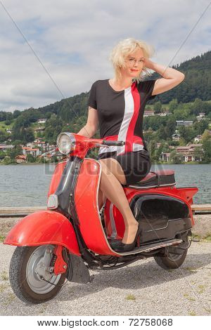 Blonde Model in a summer dress on a scooter