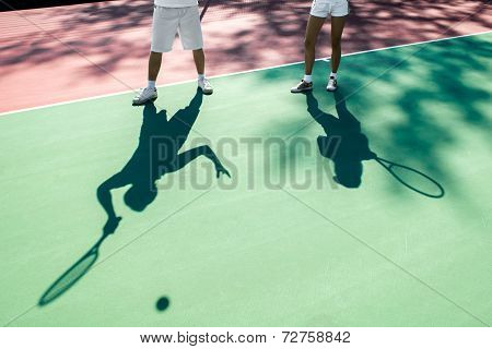 Players shadows on the tennis court