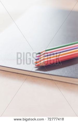 Colorful Pencils On Black Notebook