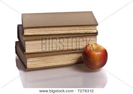 three hardback books red apple