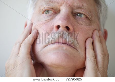 Man touches face with both hands