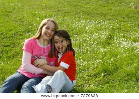 Two sisters tickling each other