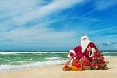 picture of christmas claus  - Santa Claus at sea beach with many gifts and decorated christmas tree  - JPG