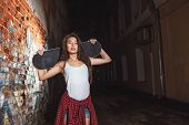 picture of skate board  - Beautiful Asian teen girl with skate board on shoulders. Outdoors, urban lifestyle. ** Note: Soft Focus at 100%, best at smaller sizes - JPG
