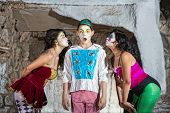 stock photo of coy  - Surprised young cirque clown with females blowing kisses - JPG