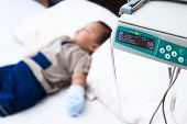stock photo of intravenous  - sick baby receiving intravenous therapy in hospital focus on infusion pump - JPG