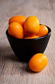 stock photo of kumquat  - Ripe orange kumquats lies in a pot of black which stands on a wooden surface - JPG