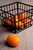 pic of kumquat  - Ripe kumquat orange lying on a wooden surface against the background of a basket filled with fruit