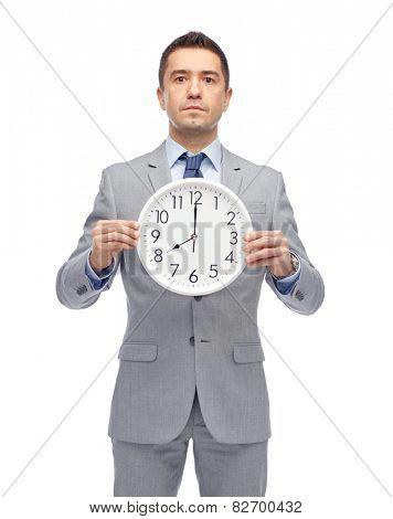 business, people, time management and office concept - businessman in suit holding clock showing 8 o'clock