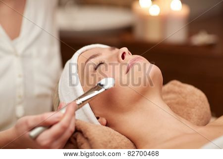 people, beauty, spa, cosmetology and skincare concept - close up of beautiful young woman lying with closed eyes and cosmetologist applying facial mask by brush in spa