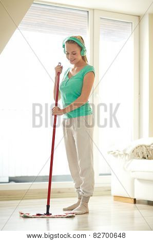 people, housework and housekeeping concept - happy woman in headphones listening to music and cleaning floor with mop at home