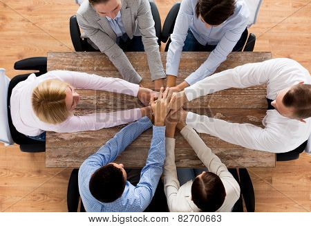 business, people, cooperation and team work concept - close up of creative team sitting at table and