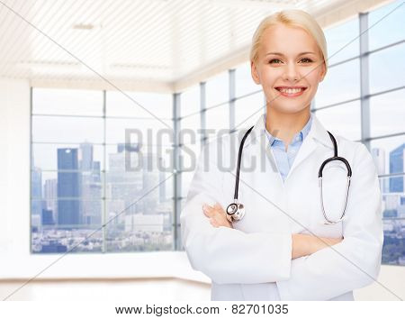 people, medicine and profession concept - smiling young female doctor over clinic background