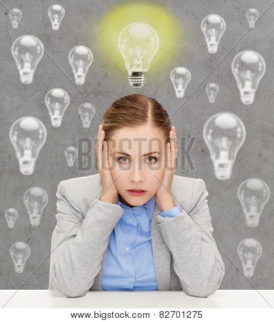 business, education, emotional pressure and people concept - stressed businesswoman or student covering her ears with hands over concrete background with light bulbs