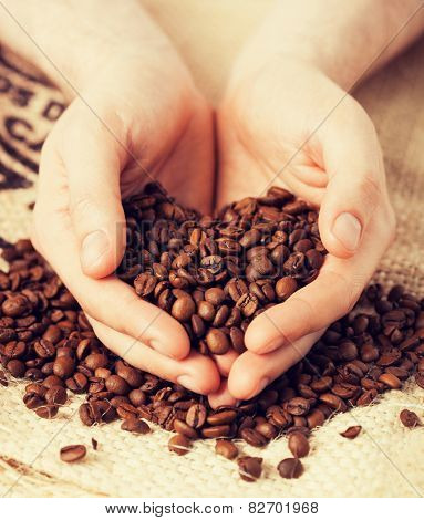 close up of man holding coffee beans