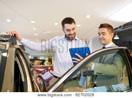 auto business, car sale, technology and people concept - happy man and car dealer with tablet pc computer in auto show or salon