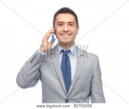 business, people and technology concept -happy businessman calling on smartphone