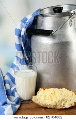 Retro can for milk with fresh bread and glass of milk on wooden table, on light background. Bio products concept