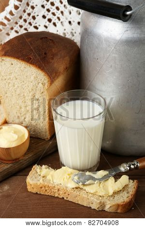 Retro can for milk with fresh bread and glass of milk on wooden background. Bio products concept