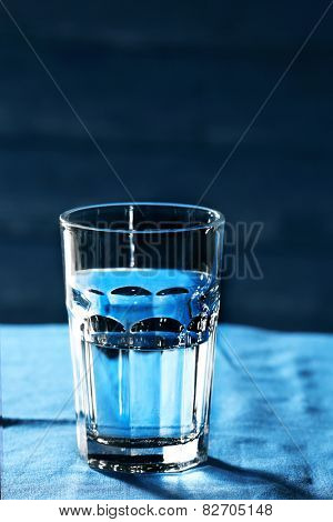 Glass of water on table on wooden background