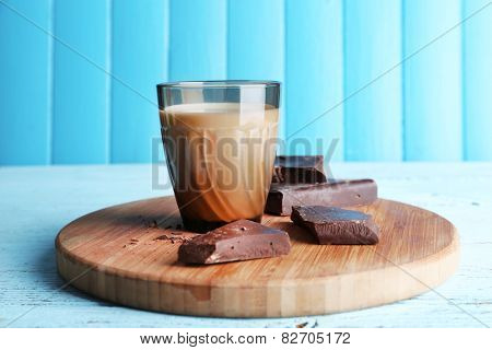 Glass of milk with chocolate chunks on cutting board and color wooden planks background