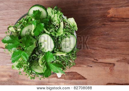 Cress salad with sliced cucumber and parsley in glass bowl on rustic wooden table background