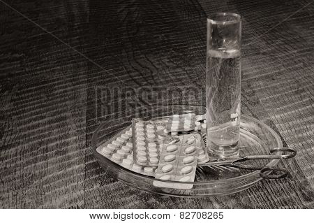 Tablets, Glass Of Water And Scissors