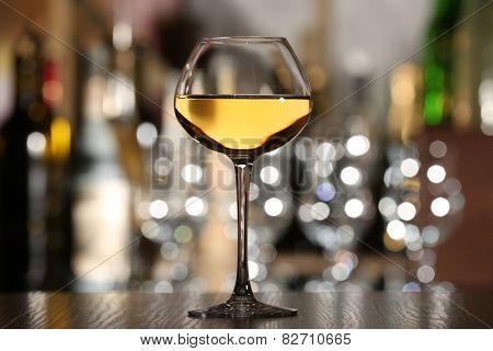 Glass of wine with bar on background