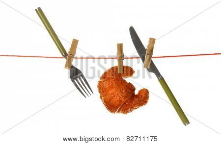 Fork, knife and croissant hanging from clothesline isolated on white background