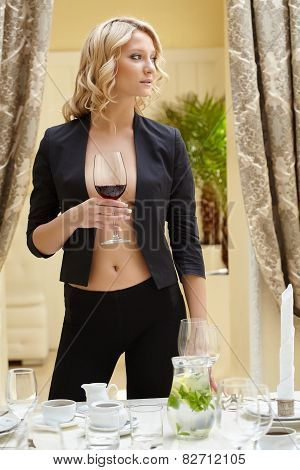 Sexy woman posing with glass of wine in restaurant