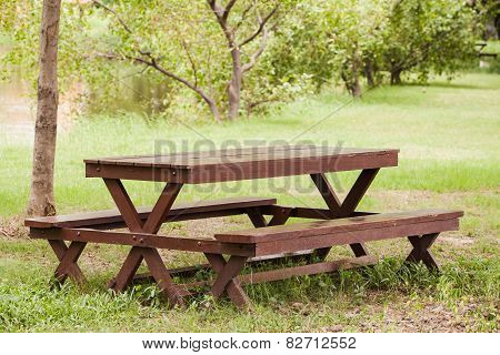 timber outdoor table and chairs in garden.