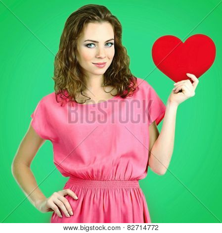 Beautiful young girl with heart in hands on green background
