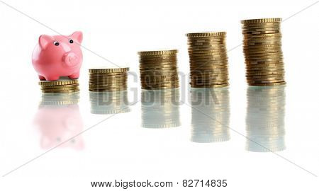 Piggy bank standing on stack of coins isolated on white