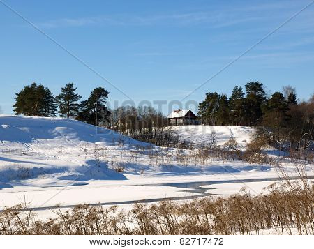 House on a steep bank of the river in winter