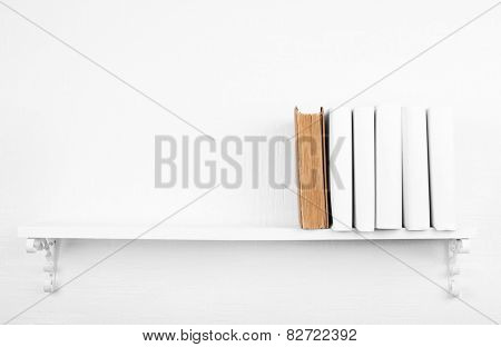 Blank books with brown one on bookshelf on white wall background