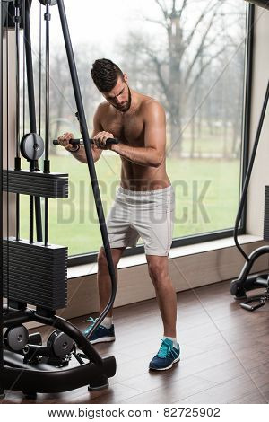 Young Man Exercising Triceps On Machine