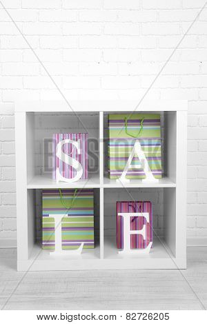 Sale with bags in shelves on bright background