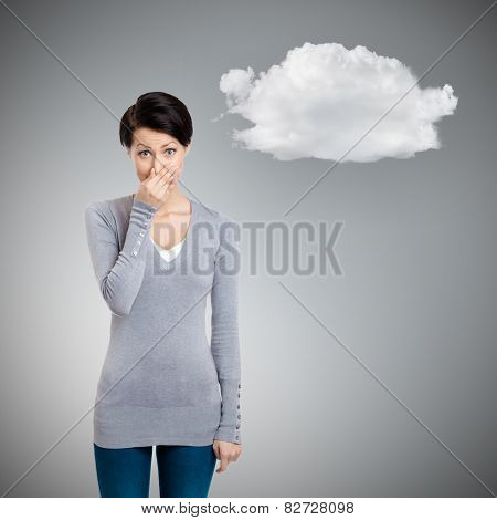 Young woman closes her nose with hand, isolated on grey background with cloud