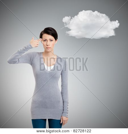 Disappointed girl shows hand gun gesture, isolated on grey background. Depression concept